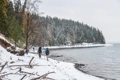 Large Group of people with backpack takes way on a snowy trail at riverside in Stock Photos