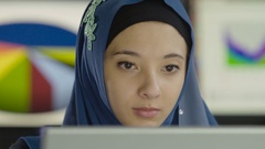 Young woman wearing a hijab working at a computer, close up shot Stock Footage