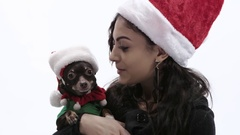 Young Brunette woman cuddles Chihuahua with Santa hat Stock Footage