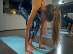 A fit woman doing plank, urdhva chaturanga dandasana on mats in a yoga studio Stock Footage