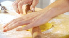 A woman is baking cookies making the shortbread using flour and a rolling pin Stock Footage