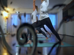 Group of people doing Warrior I Pose, Virabhadrasana I on mats in a yoga studio Stock Footage