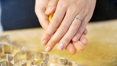 Woman's hand shows a heart shaped shortbread cookie in the kitchen Stock Footage