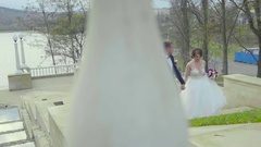 Frontview of a wedding couple walking up to stairs and holding hands Stock Footage