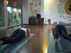 People doing downward facing dog, Adho Mukha Svanasanan on mats in a yoga studio Stock Footage