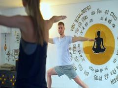 A man showing the Warrior II Pose, Virabhadrasana II on a mat in a yoga studio Stock Footage