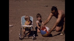 Father with little girl and baby play with beachball at beach Stock Footage