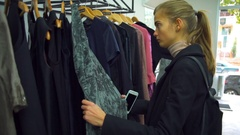 A young beautiful woman and a man looking at the clothes in a shop Stock Footage
