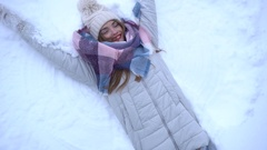 Girl lying in the white snow and making an angel Stock Footage