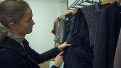 A young beautiful woman choosing stylish clothes in a shop Stock Footage