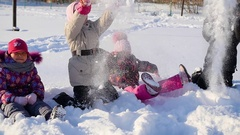 Cheerful children playing in the snow throwing snow up in park Stock Footage