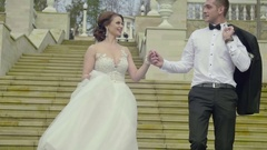 Bride and groom look at each other walking downstairs outside Stock Footage