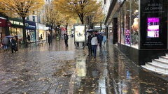 Various people with umbrellas shopping in the rain in Nottingham. Stock Footage