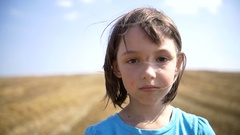 Young refugee homeless girl looking to the camera in the field , scratched face Stock Footage