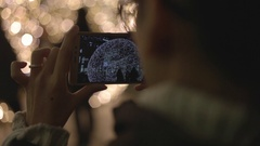 Woman takes picture of Snow Globe Lighting Stock Footage