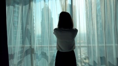 Young businesswoman unveil curtain and looking out of window in the office super Stock Footage