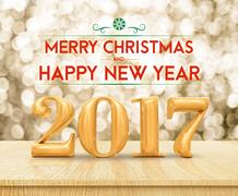 Golden color 2017 Merry Christmas and HappyNew Year (3d rendering) on wood .. Stock Photos