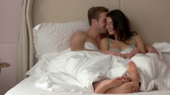 Guy with girl in bed. Stock Footage