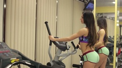 Sexy girl training on orbitrek. Girl is running on elliptical trainer in gym. Stock Footage