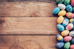 Colorful pastel easter eggs on wooden background with space. Vintage toned. Kuvituskuvat