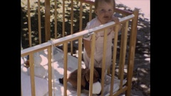 Happy baby girl in crib shows off stuffed animal Stock Footage