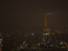 Zoom-in Fast motion Eiffel Tower aerial at night with lighthouse light above Stock Footage