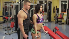 Beautiful cute girl is engaged in the gym with a personal trainer. Stock Footage