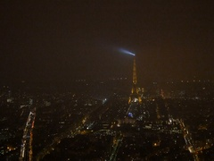 Zoom-in to Eiffel Tower aerial at night with lighthouse light above Paris Arkistovideo