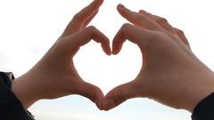 Sun shining through heart shaped hands Stock Footage