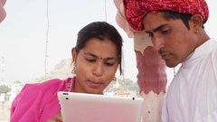 Rajasthani couple working learning teaching sharing on a tablet wearing pink sar Stock Footage
