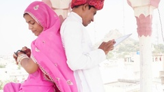 Couple busy on their smart watch and tablet sepreately ignoring with their backs Stock Footage