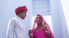 Woman in pink sari and man in red turban with light blue background pose for cam Stock Footage