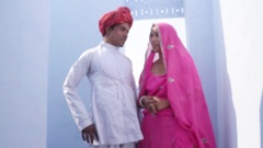 Focus shift to a gorgeous traditional bride and groom in traditional wear agains Stock Footage