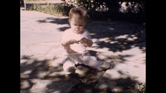 Curious baby girl picking grass and leaves Stock Footage