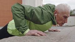 Senior Man Doing Push-Ups on Sidewalk Stock Footage
