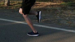 Sportsman running along the road. Athletic legs. Slow motion Stock Footage