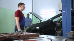 Mechanic raises the car on the car lift Stock Footage