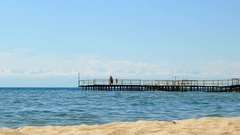 People on the pier against mountains. Issyk Kul Lake. Cholpon Ata, Kyrgyzstan Stock Footage