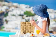 Young woman with coffee at outdoor cafe with amazing view on Mykonos town Stock Photos
