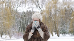 Pretty girl drinking a cup of hot beverage outdoor in winter day Stock Footage