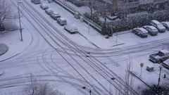 Aerial view of four way traffic flow on cold blizzard snow winter day Stock Footage