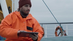 Casualy Dressed Fisherman Using Tablet Computer with Navigation Maps while Trave Stock Footage