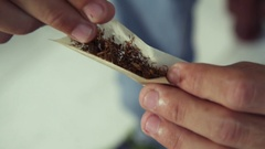 Man Preparing Hashish Joint Rolling Marijuana Cigarette For Smoking Stock Footage