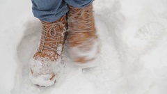 The legs of a man in blue jeans and red boots shifting in the snow Stock Footage
