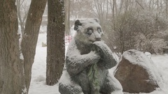 Stone statue of sitting panda during a snowfall on a winter day Stock Footage
