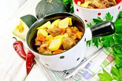 Roast meat and vegetables in white pots on board Stock Photos