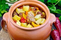 Roast meat and vegetables in clay pot on burlap Stock Photos