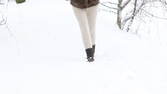 Pretty girl walking in the park in snow-white day. Slowly Stock Footage