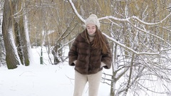 Happy smiling girl walking and looking back in the park in snowy day. Slowly Stock Footage