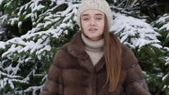 A lump of snow falling on the girl standing near tree. Slow motion Stock Footage